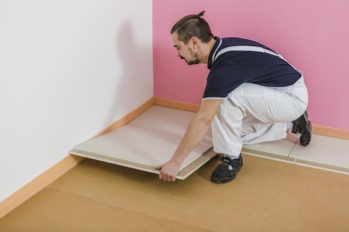 Pokládka podlahových dílců přes spáru dřevovláknitých desek.