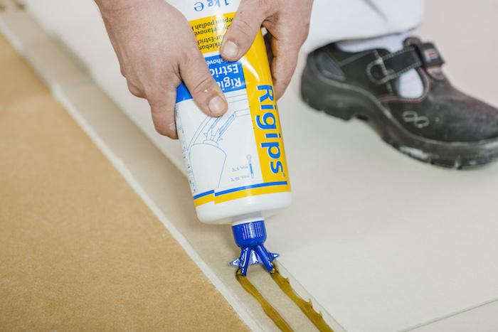 Nanesení podlahového lepidla Rigidur do polodrážek podlahových dílců